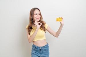 retrato de uma linda mulher asiática segurando um cartão de crédito no fundo branco foto