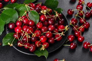 Frescas deliciosas bagas vermelhas brilhantes de cereja rasgadas no jardim de verão foto