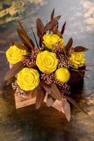 buquê de lindas flores rosas amarelas brilhantes em uma caixa de presente foto
