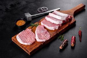 um pedaço cru fresco de escalop de porco cortado em várias partes foto