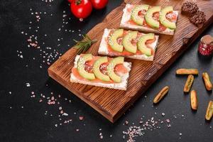 delicioso sanduíche fresco com peixe vermelho, manteiga, pão e abacate foto