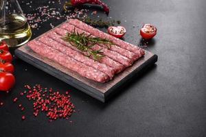 linguiça de porco crua fresca com especiarias em uma tábua de madeira foto