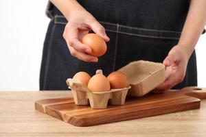 mulher segurando ovos de galinha frescos em caixa de papelão foto