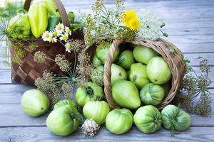 vegetais em uma cesta e um buquê de flores silvestres foto