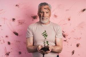 homem sênior, jardineiro segurando uma planta para plantar em um fundo foto