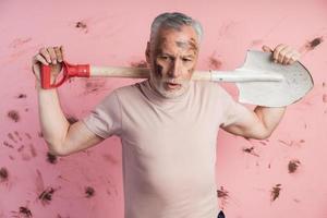 homem sênior cansado com o rosto sujo segurando uma pá nos ombros foto
