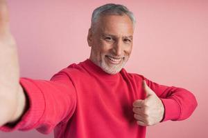 atraente, idoso tirando uma selfie, polegar para cima, tudo legal foto