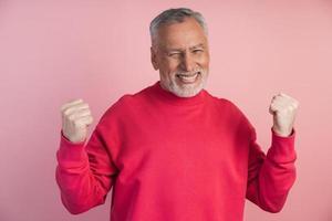 homem sênior, alegre, posando em um fundo rosa foto