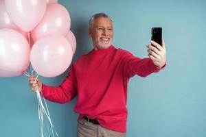 sênior atraente segurando balões e tirando uma selfie foto