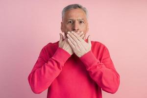 homem sênior gesticulando em um fundo rosa foto