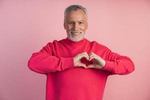 homem mais velho mostra um gesto do coração foto