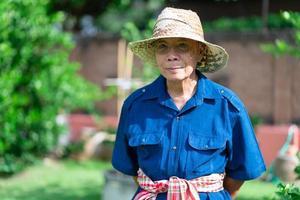 retrato de um fazendeiro sênior asiático com um rosto sorridente em pé na fazenda foto