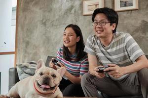 casal asiático está jogando videogame e cachorro de estimação nas proximidades. foto