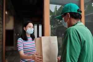 entregador com máscara facial dá um pacote para uma mulher asiática. foto