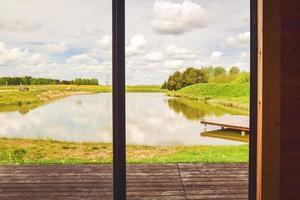 panorama panorâmico calmo pequeno lago com ponte de madeira foto