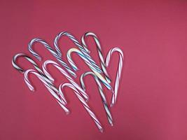 bengala de caramelo de doces de Natal feliz em um fundo rosa foto