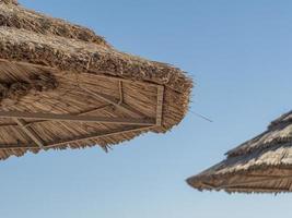 telhado de palha do guarda-sol e céu azul ao fundo foto