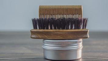 escova de barba, pente de madeira para barba e frasco de cera para barba e bigode foto