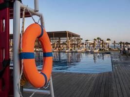 bóia salva-vidas laranja perto de uma piscina pública em um fundo desfocado foto