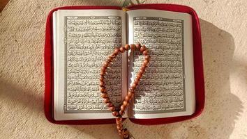 foto do Corão e contas de oração que são símbolos do Islã