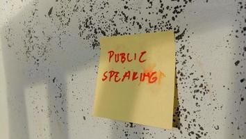 texto com as palavras falando em público em uma nota colada na parede foto