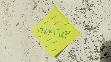 texto com as palavras start-up em uma nota postada na parede foto