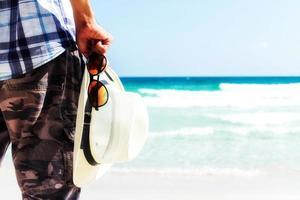 close-up turista segurando chapéu de palha e óculos escuros foto