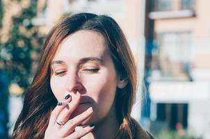 garota atraente fuma um cigarro ao ar livre foto