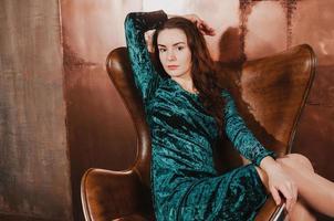 bela jovem em uma cadeira de couro marrom foto