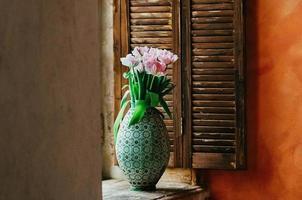 um buquê de flores em foco suave em um vaso no parapeito de uma janela foto