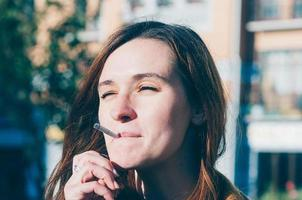 mulher muito fofa fumando um cigarro na rua foto