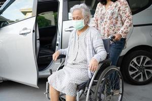 ajudar mulher asiática sênior em cadeira de rodas a se preparar para chegar ao carro foto