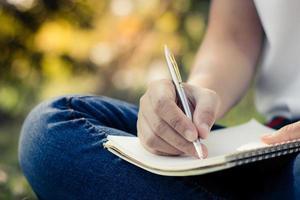 fechar mulheres jovens escrevendo no caderno no parque foto
