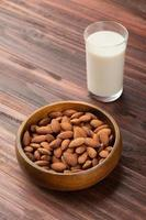 leite de amêndoa no copo com amêndoas em tigela de madeira em cima da mesa foto