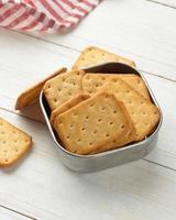 biscoitos cracker em uma tigela de aço inoxidável com toalha de mesa foto