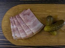 bacon e picles em uma placa de madeira. lanche tradicional russo foto