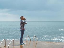fotógrafo profissional com uma câmera tira uma foto do mar