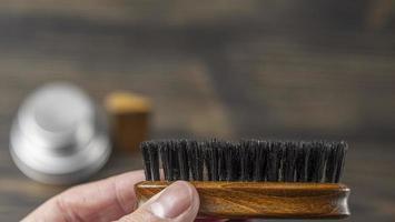 escova de barba em uma mão masculina em um fundo desfocado foto