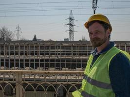 homem de capacete fica em uma ponte perto dos trilhos da ferrovia foto