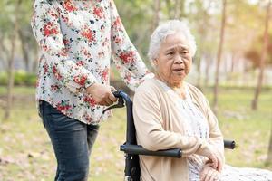 paciente sênior asiática em cadeira de rodas no parque. foto