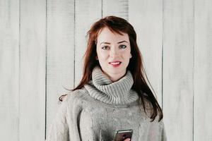 uma linda menina morena segurando um celular, sorrindo alegremente foto