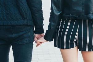 vista traseira de um jovem casal de jaquetas pretas, de mãos dadas foto