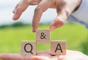 q e um alfabeto em um cubo de madeira na mão segure com o fundo foto