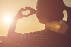 jovem mulher com as mãos em forma de coração contra o belo pôr do sol. foto
