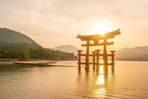 o portão flutuante do santuário itsukushima ao pôr do sol foto