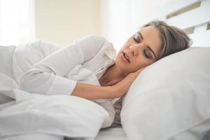bela jovem dormindo na cama foto