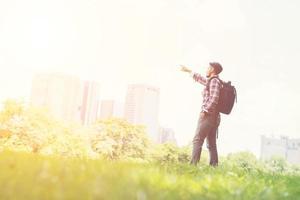 jovem hippie apontando para a vista da cidade do parque enquanto mochila foto