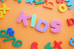 letras de plástico coloridas em fundo laranja, vista superior foto