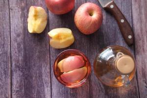 vinagre de maçã em vidro com maçã fresca na mesa, vista superior foto