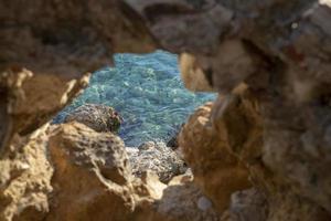 olhando através de uma pequena caverna no mar foto
